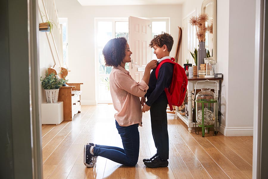 Personal Insurance - Mom Kneels in a Large Hallway to Straighten Her Son's Red Backpack on His Shoulders, Front Door Open and Sun Shining Through