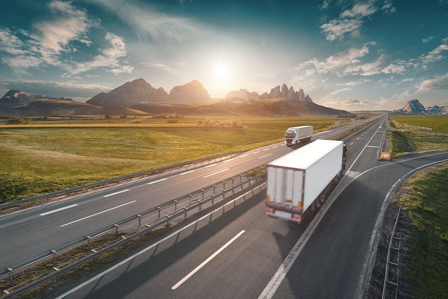 Specialized Business Insurance - Two Trucks on a Highway Traveling Long Distance in the Morning With Sunrise in the Distance