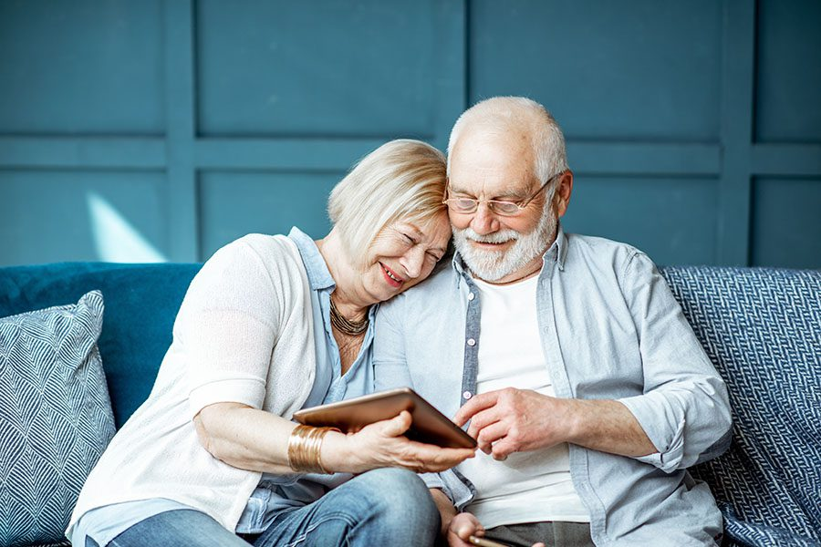 Client Center - Portrait of a Happy Mature Couple Sitting on the Sofa at Home While Using a Tablet Together