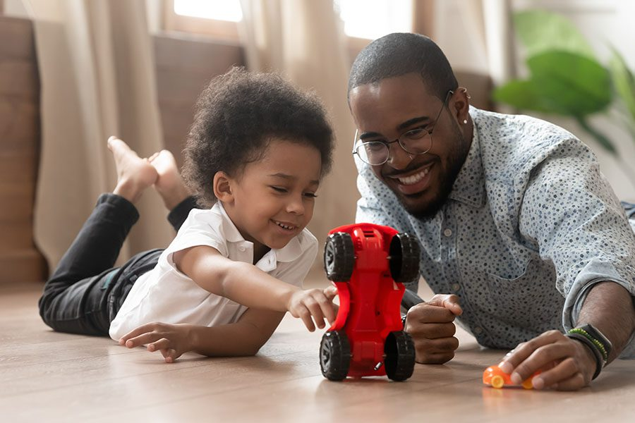 Insurance Quote - Closeup Portrait of a Father and Son Having Fun Playing at Home with Toy Cars