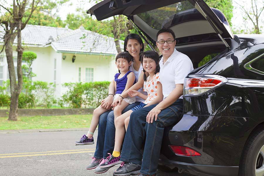 Personal Insurance - Happy Family with Two Kids Sitting in the Back Trunk of Their Car While Parked Next to Their House