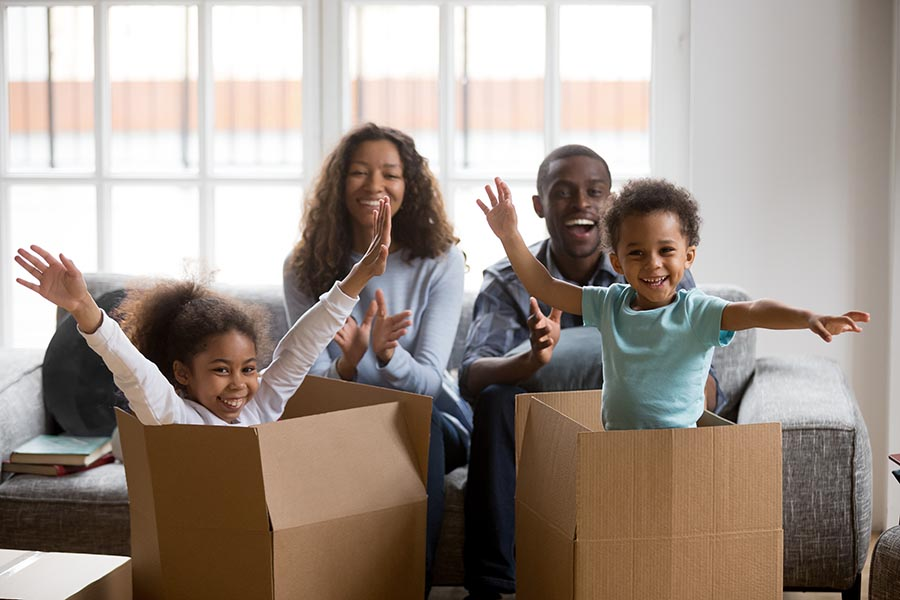 Blog - Family Celebrates Moving Into Their New Home, Kids Playing in Cardboard Boxes, Parents Clapping