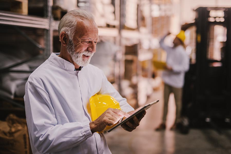 Client Center - Senior Businessman Uses a Tablet in a Warehouse, Yellow Hard Hat Under His Arm
