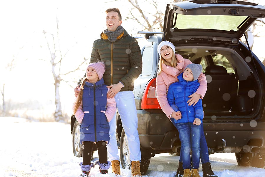 Personal Insurance - Family in Winter Gear Stands Outside Their Car in a Light Snow on a Bright Sunny Day