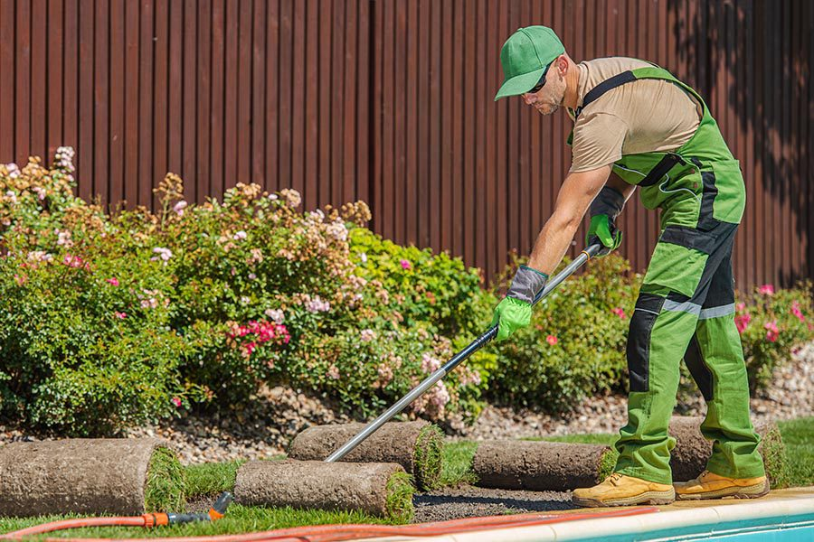 Specialized Business Insurance - a Landscaper in Cap and Overalls Lays Out Sod Along the Edge of a Swimming Pool