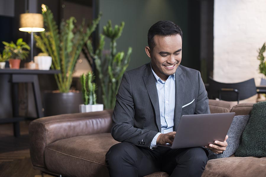Blog - Businessman Uses a Computer on a Leather Couch in an Office Lobby, Potted Cacti Behind Him