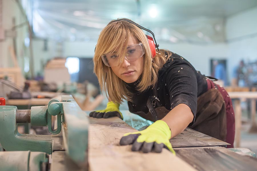 Business Insurance - Carpenter Planes a Piece of Lumber in a Shop, Wearing Protective Gear