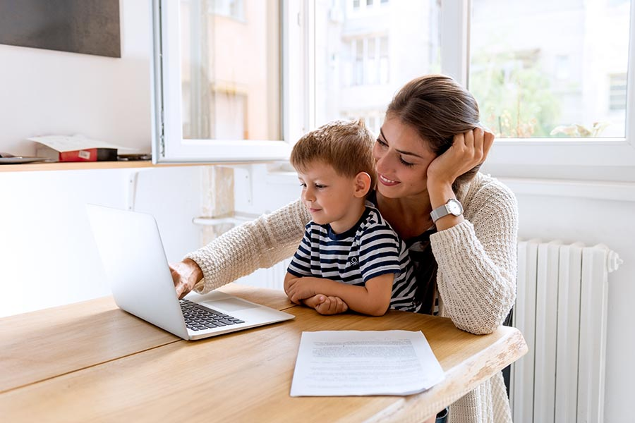 Client Center - Mom Uses Computer at Kitchen Table, Young Son Perched on Her Lap Watching