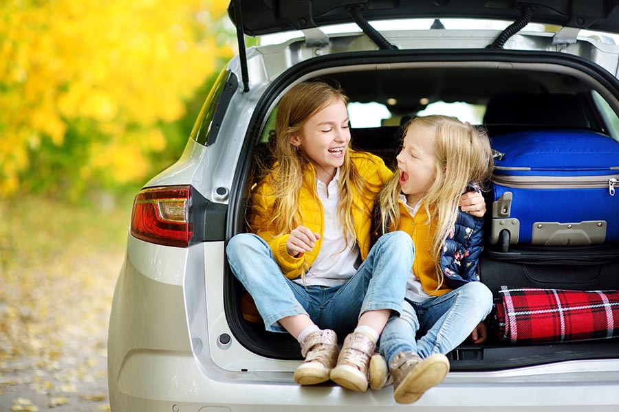 Contact Us - Kids Sitting in the Back of a Car, Ready for a Road Trip, Bags Packed in the Trunk