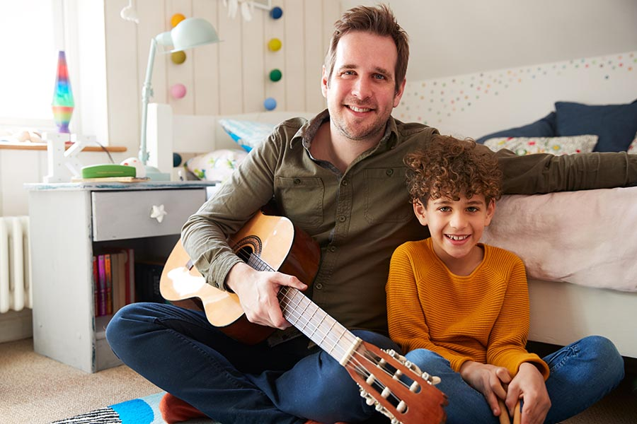 Personal Insurance - Father and Son Sit on Son's Bedroom Floor, Dad Holding an Acoustic Guitar, Both Smiling
