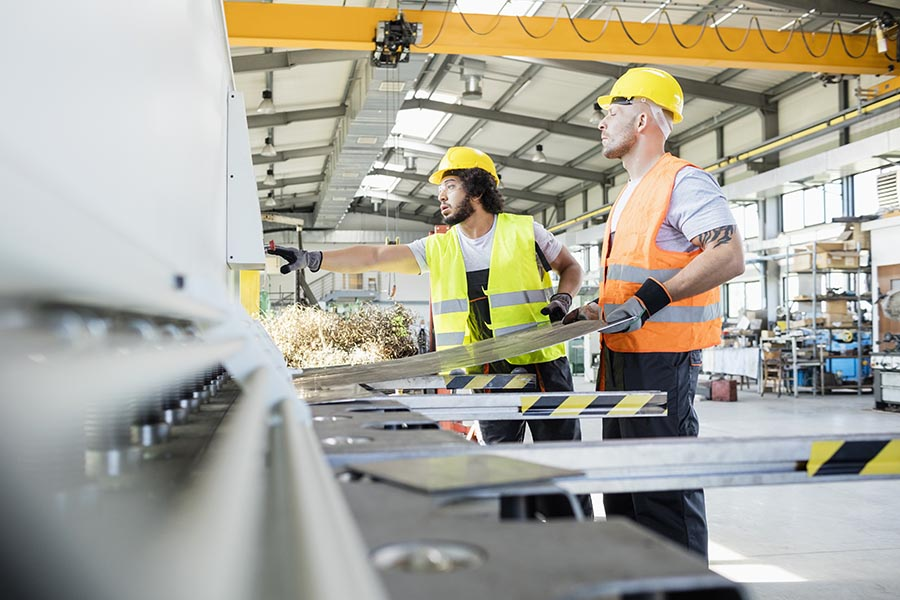 Specialized Business Insurance - Workers Consult Over a Project in a Manufacturing Facility, Wearing Hard Hats and Reflective Vests