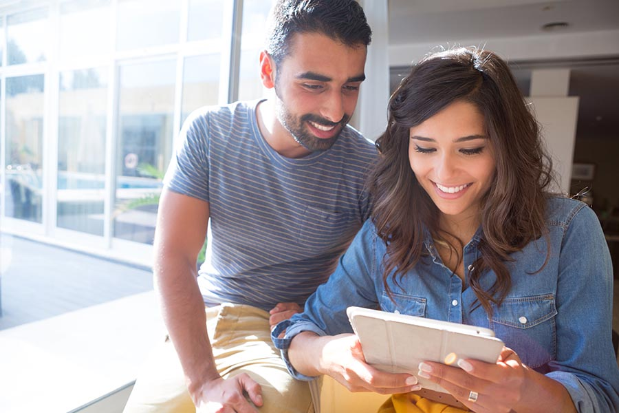 Get a Quote - Couple Using a Tablet, Smiling and Sitting Close by a Large Window