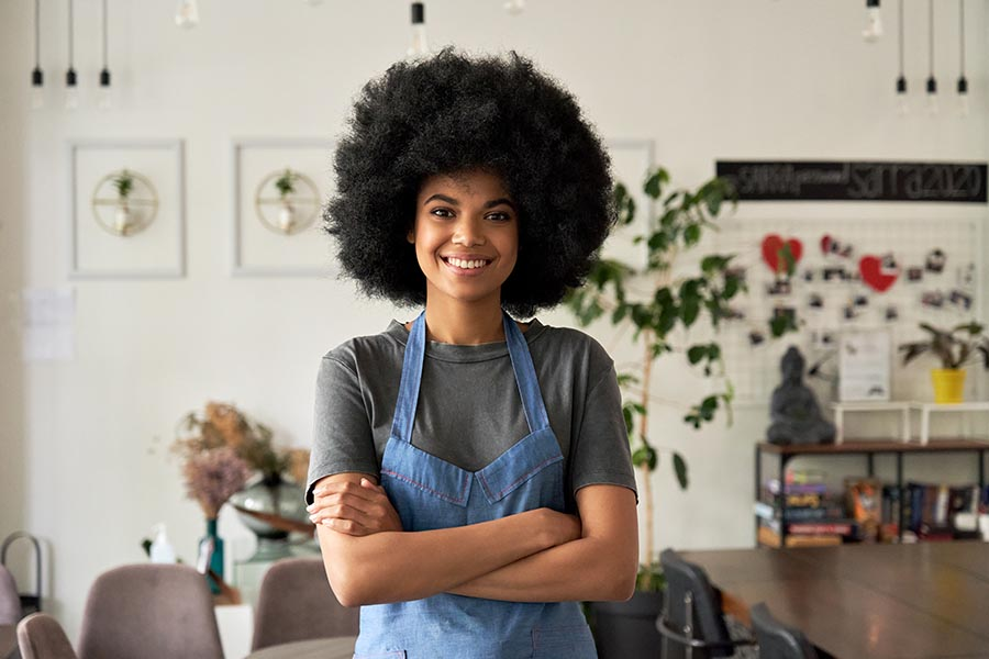 Business Insurance - Small Business Owner Standing in Her Shop, Wearing a Blue Apron, Smiling