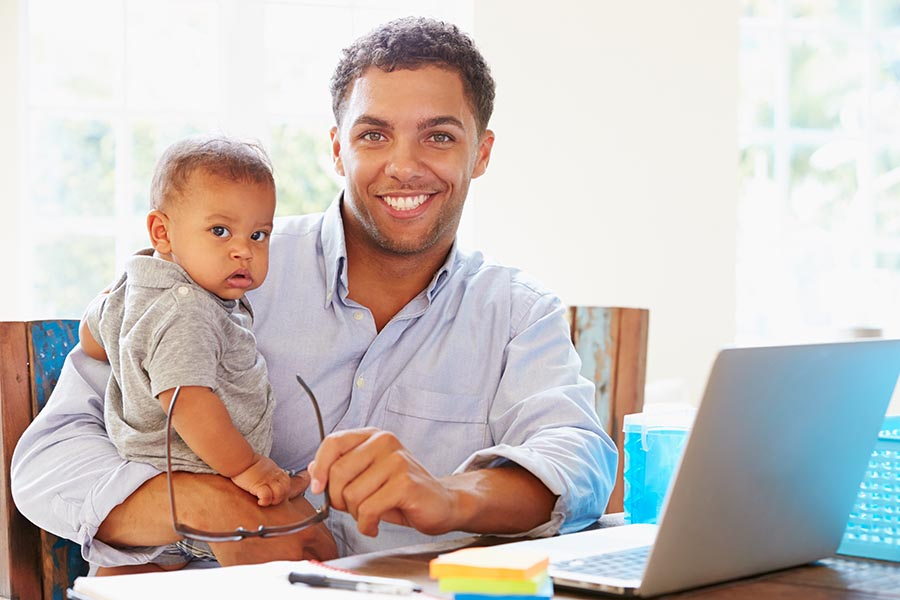 Client Center - Father Holding Baby Uses a Computer at the Kitchen Table