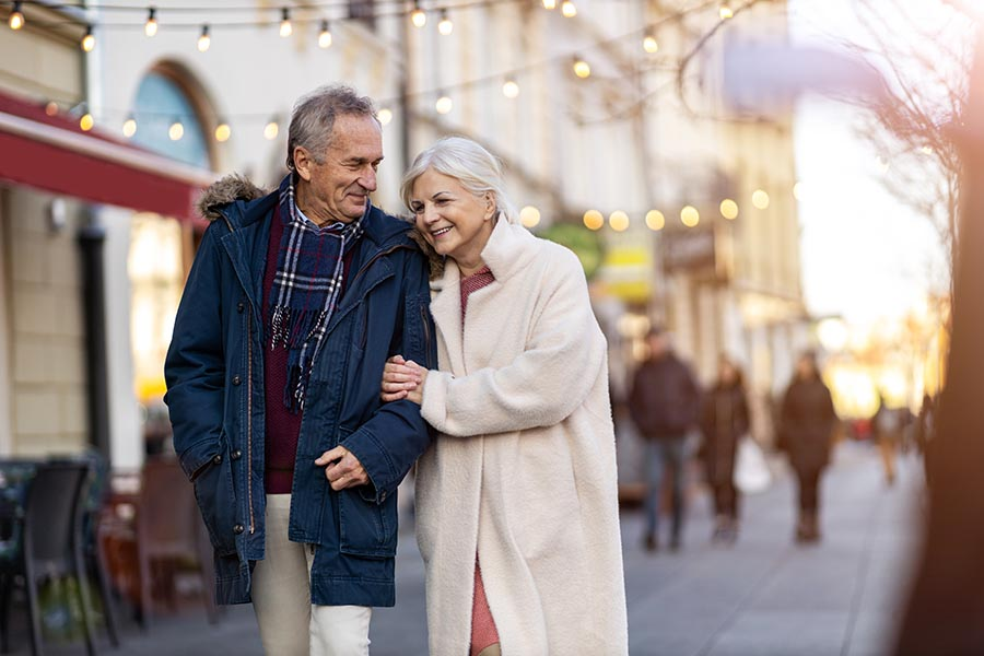 Homepage - Senior Couple Strolling Through the City in Winter Coats, Wife Holding Husband's Arm