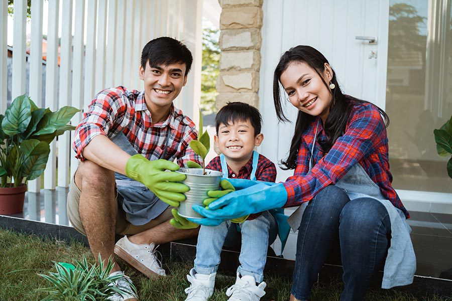 Personal Insurance - Father, Young Son, and Mother Sit on Their Back Patio, Wearing Gardening Gloves and Planting Greenery in Their Yard