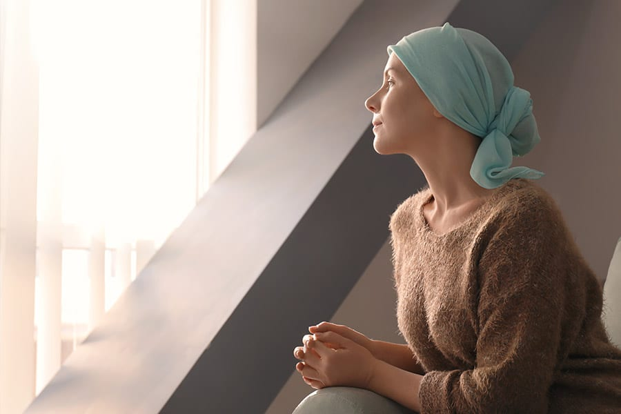 Critical Illness Insurance - A Woman with Cancer Sitting and Looking Out a Hospital Window