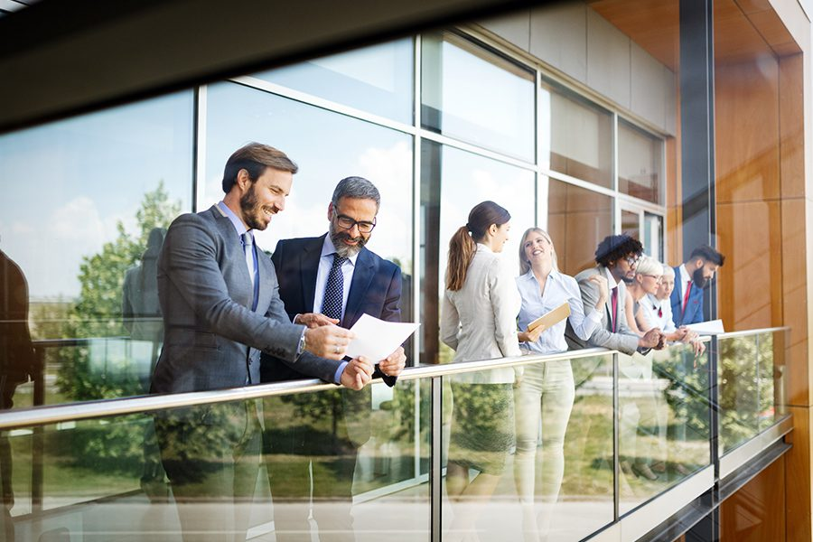 Business Insurance - Business Colleagues Talking Over Break on the Balcony of a Modern Office
