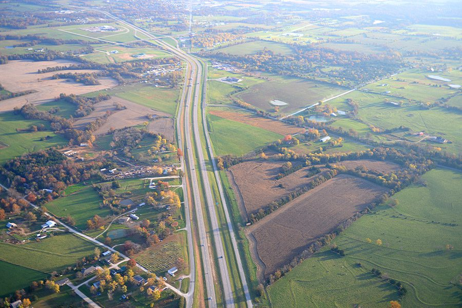 Contact - Aerial View of Midwest Town and Farmland on a Summer Day