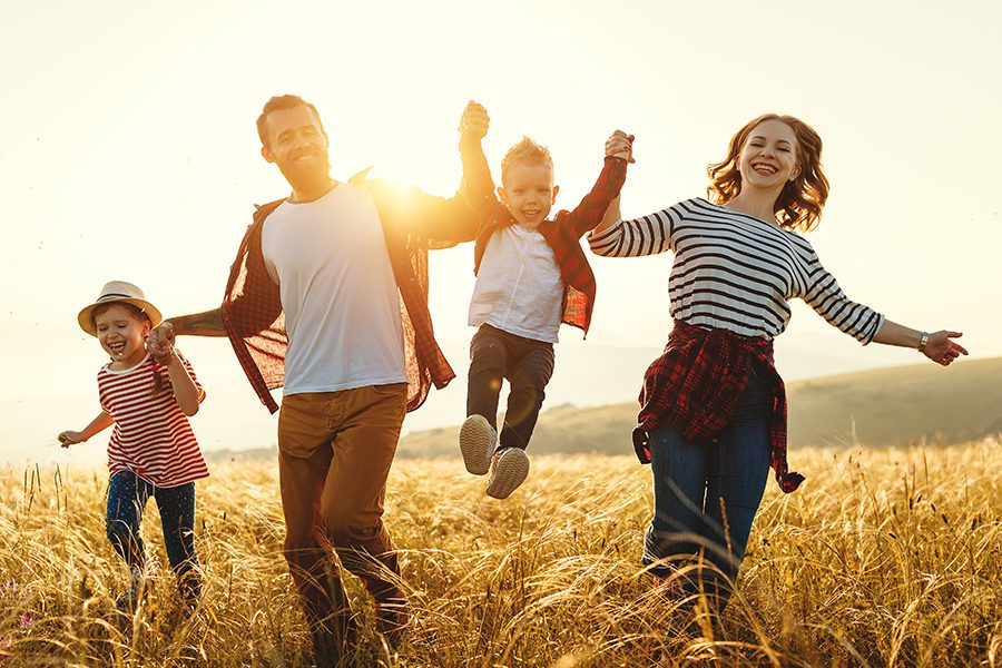 Personal Insurance - Happy Family Holding Hands While Running in a Field at Sunset