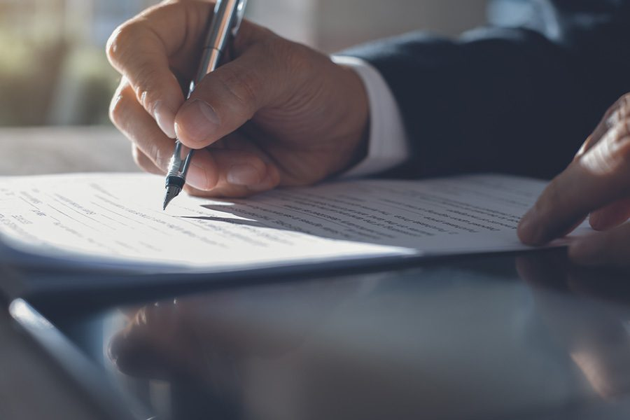 Contract Surety Bonds - Closeup of Businessman Signing Contract in an Office