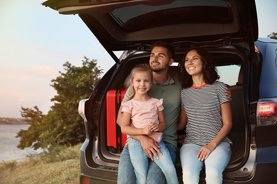 About Our Agency - Mother, Father and Young Daughter Sit in the Back of Their Open Car by a Lake, Looking off at the Sunset