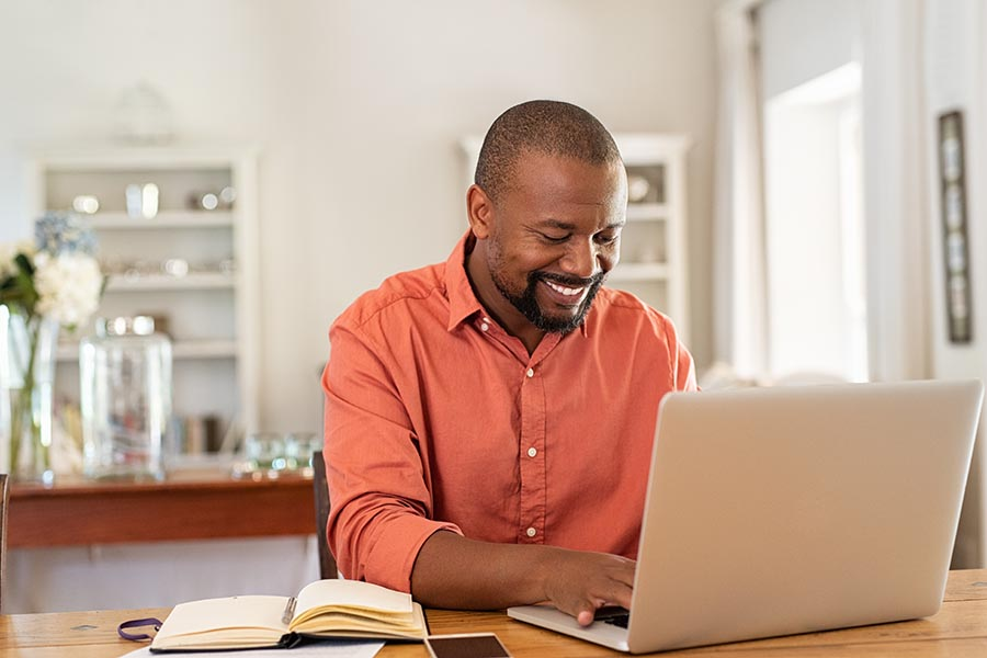 Client Login - Smiling Man in an Orange Button Down Shirt Uses His Laptop at a Large Wooden Desk