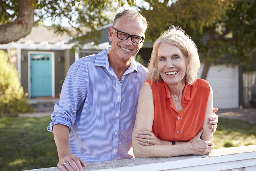 Contact Us - Senior Couple Stand at the Gate in the Front Yard of Their Small Suburban Home, Smiling Together