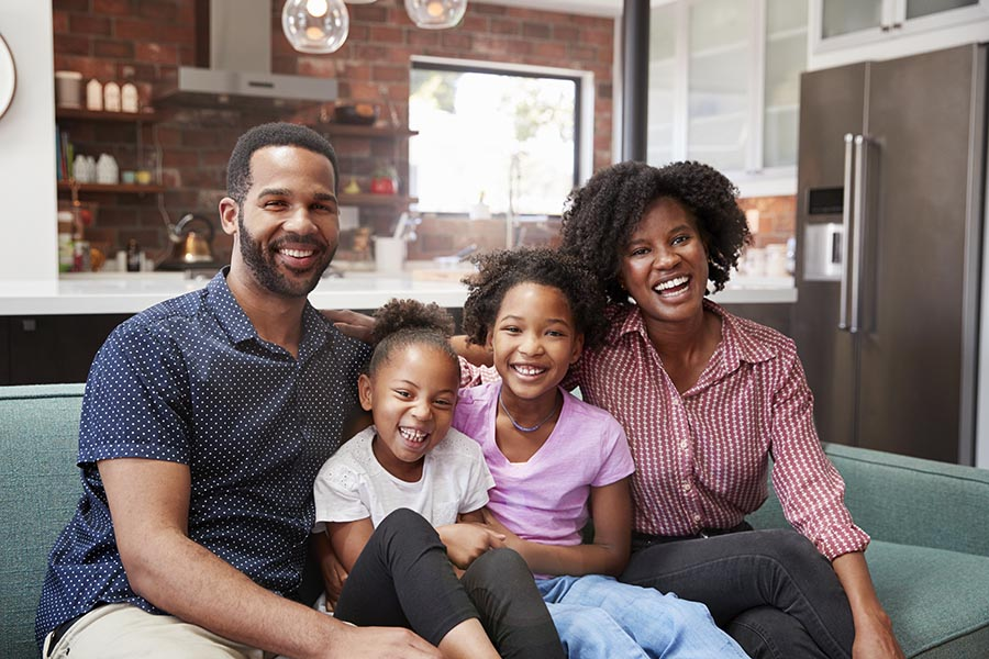 Personal Insurance - Young Family Sit on Their Sofa in a Nice Living Room, Snuggled Closely Together and Smiling, Large Kitchen Behind Them
