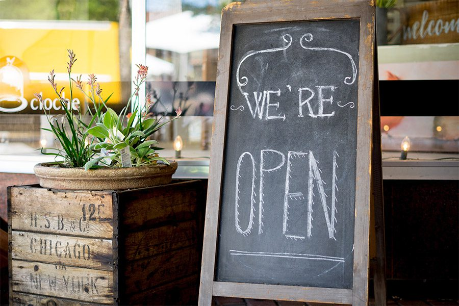 Business Insurance - Farmhouse Style We're Open Sign Outside of a Small Business
