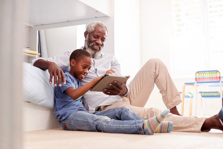 Client Center - Grandfather with Grandson Looking at a Tablet on Grandson's Bedroom Floor