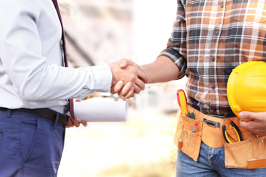 Specialized Business Insurance - Male Architect and Builder Shaking Hands Outdoors at a Construction Site