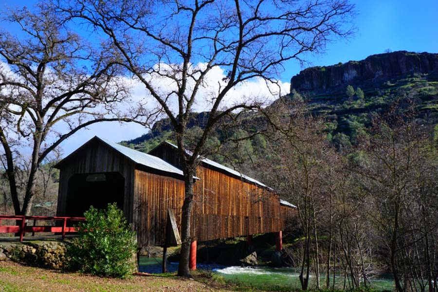 About Our Agency - View of the Honey Run Covered Bridge Over a Creek Next to a Mountain in Chico California
