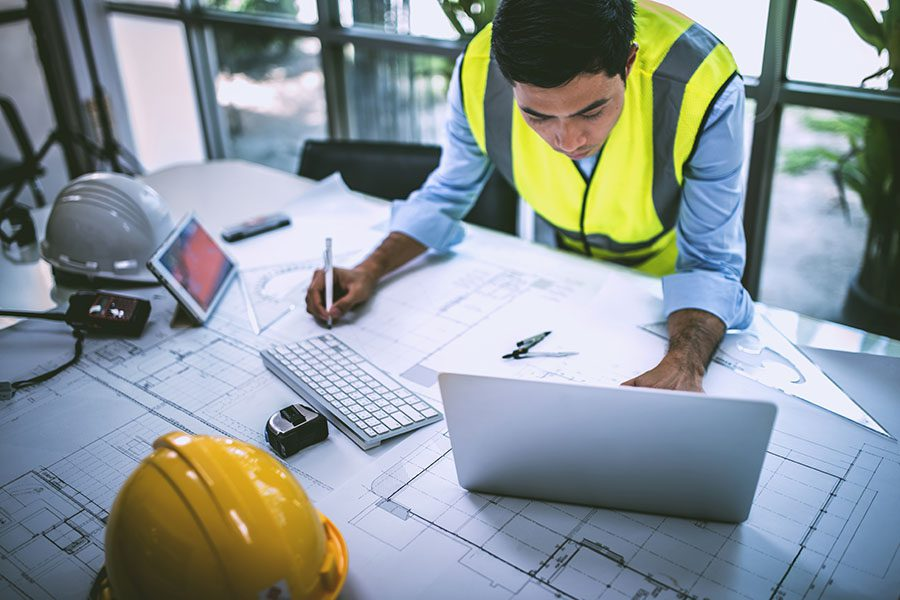 Business Insurance - Portrait of a Contractor Working on New Building Plans on His Laptop in an Office with Blueprints on His Desk