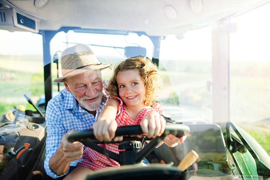 Employee Benefits - Closeup Portrait of a Cheerful Grandfather Riding in a Tractor with His Excited Granddaughter on Their Farm on a Warm Summer Day