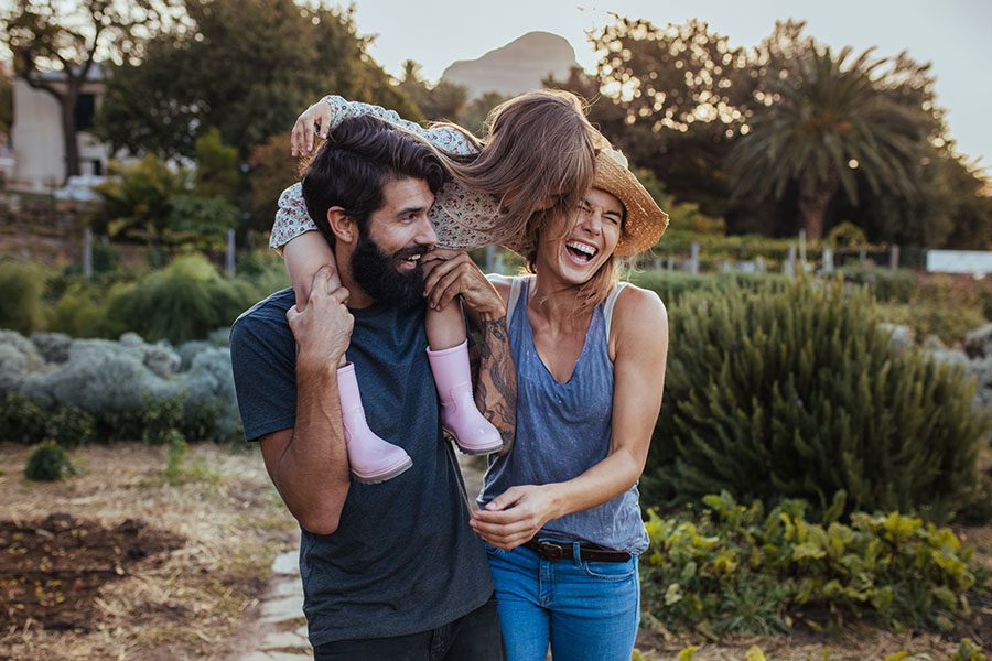 Personal Insurance - Portrait of a Cheerful Family with a Young Girl Getting a Piggyback Ride While Walking Through Their Farm