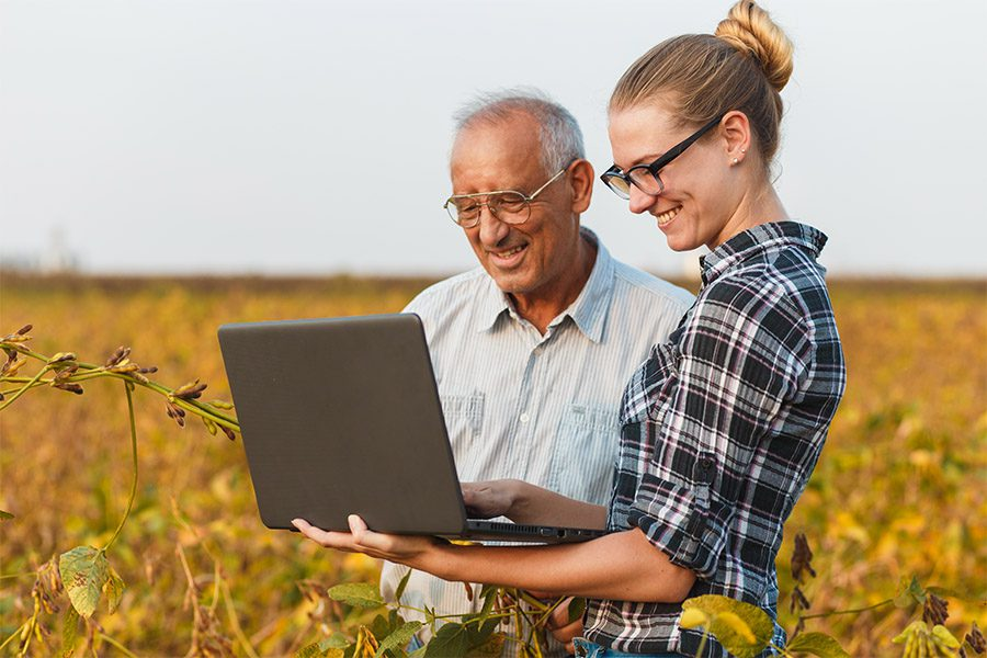 Blog - Older Man and Younger Female Smiling and Standing in a Farm Field While Looking at a Laptop on a Beautiful Day