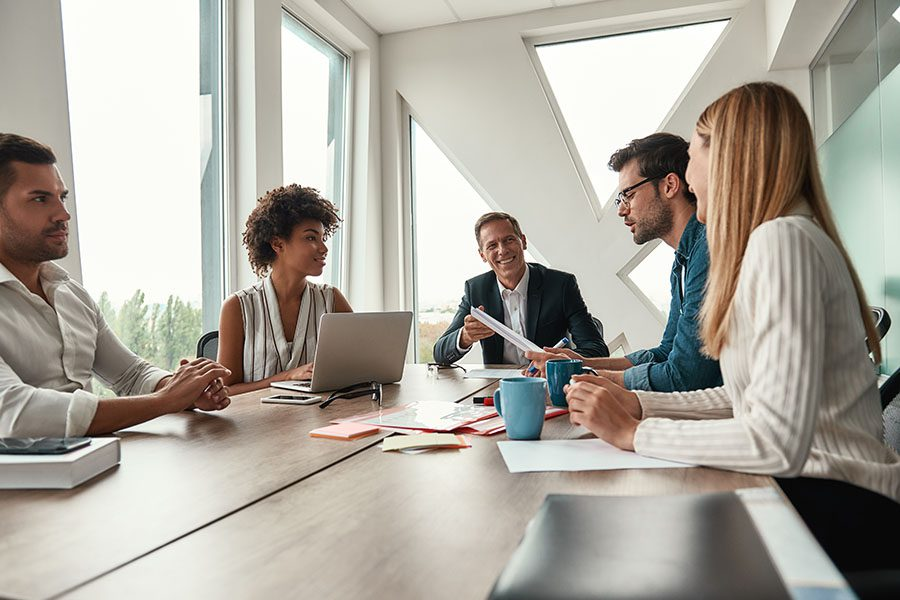 Business Insurance - Group of Employees Sitting in a Modern Office During Business Meeting