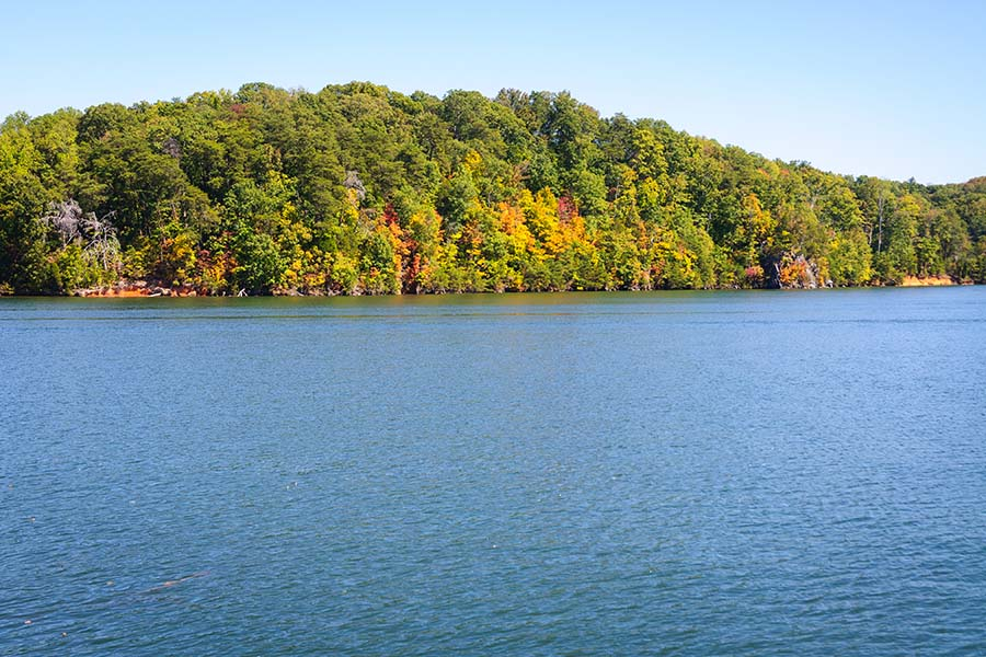 Madisonville TN - View of Calm Lake and Trees in the Early Fall Against Blue Sky in Madisonville Tennessee