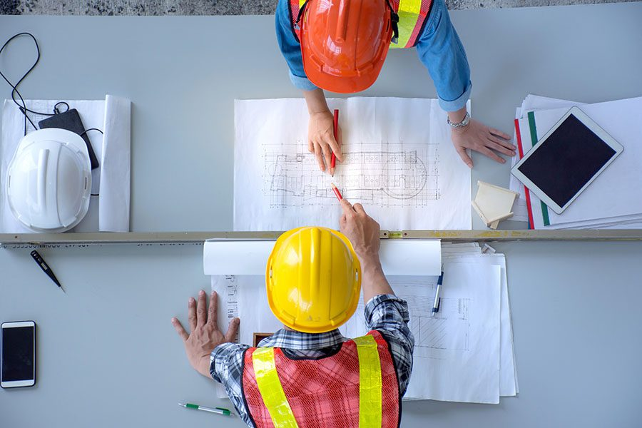 Specialized Business Insurance - Two Contractors Examining New Building Blueprints in the Office