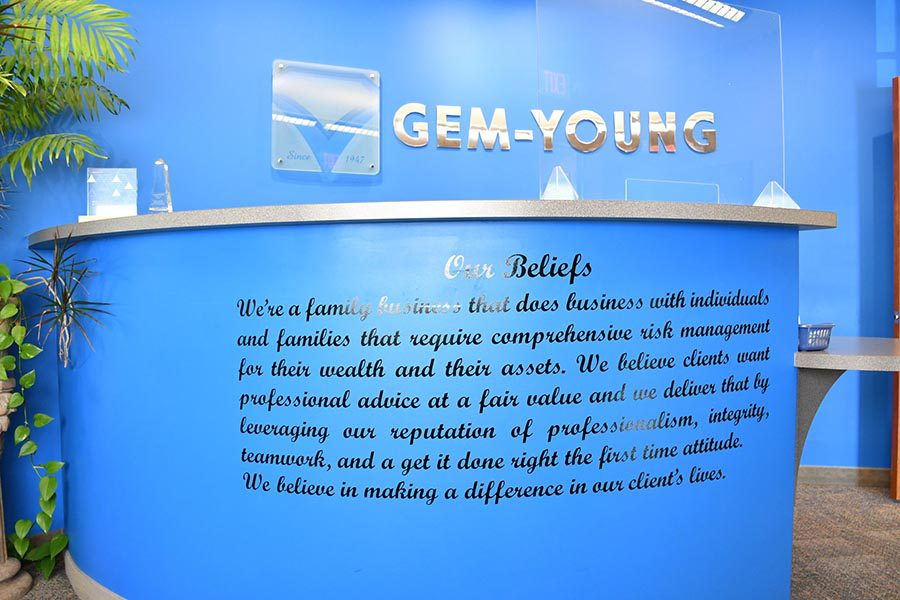 About Our Agency - View of Blue Office Reception Area, Logo Sign, and Gem-Young Insurance & Wealth Advisors Belief System Written on the Front of Desk