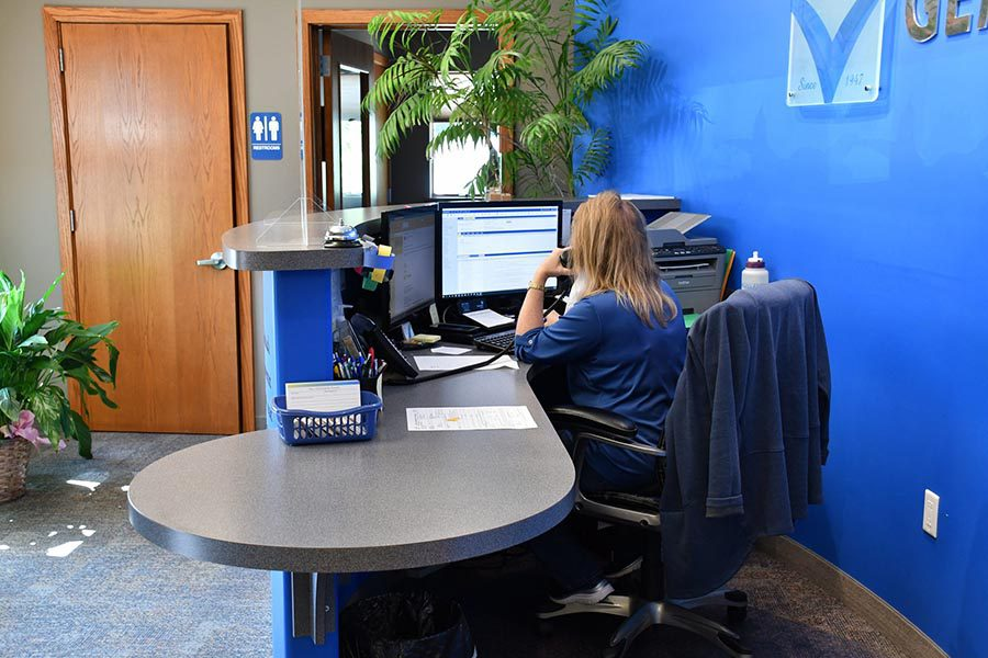Client Center - Gem-Young Insurance & Wealth Advisors Employee Answering Calls at Her Desk