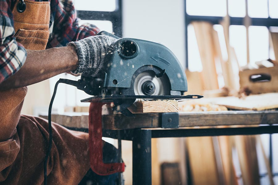 Specialized Business Insurance - Closeup of Contractor Using Circular Saw in Workshop