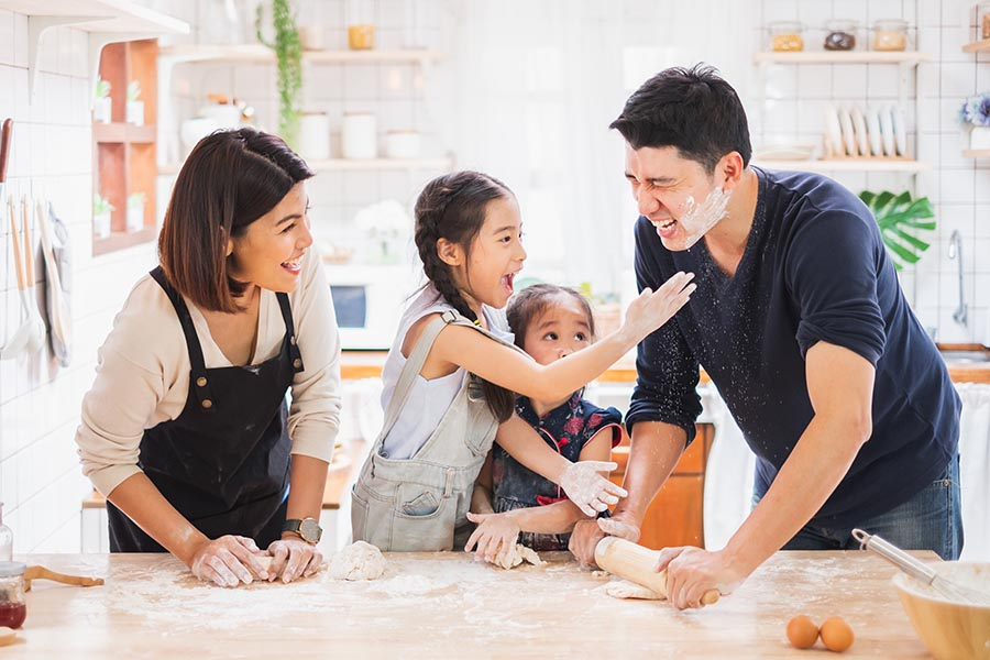 Personal Insurance - Family Rolls Out Cookie Dough, Kids Covering Their Parents With Flour, in Their Bright White Kitchen
