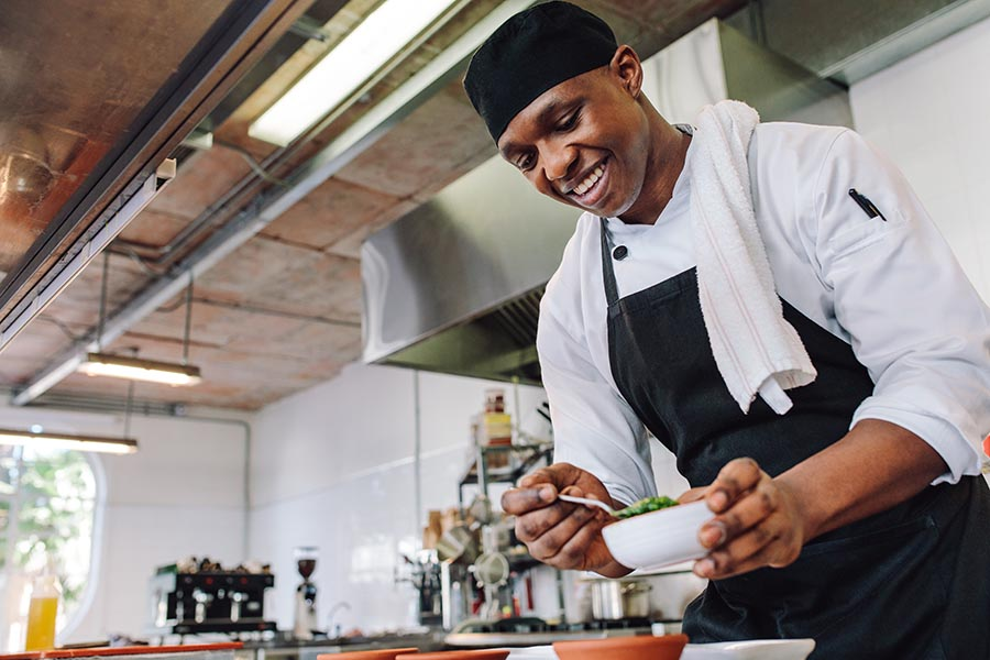 Specialized Business Insurance - Chef Prepares Meals in a Beautiful Modern Kitchen in a Restaurant, Wearing a Black Apron and Cap