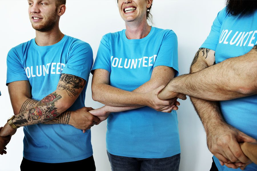 Non-Profit Insurance - Volunteers Holding Hands and Embracing