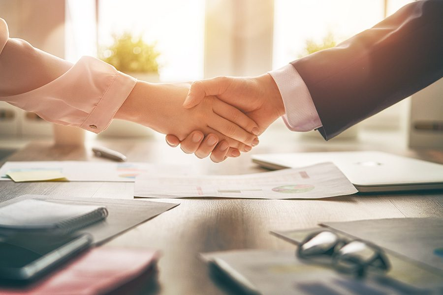 About Our Agency - Closeup View of a Business Handshake in the Office Over a Wooden Desk with Documents and Glasses on Top