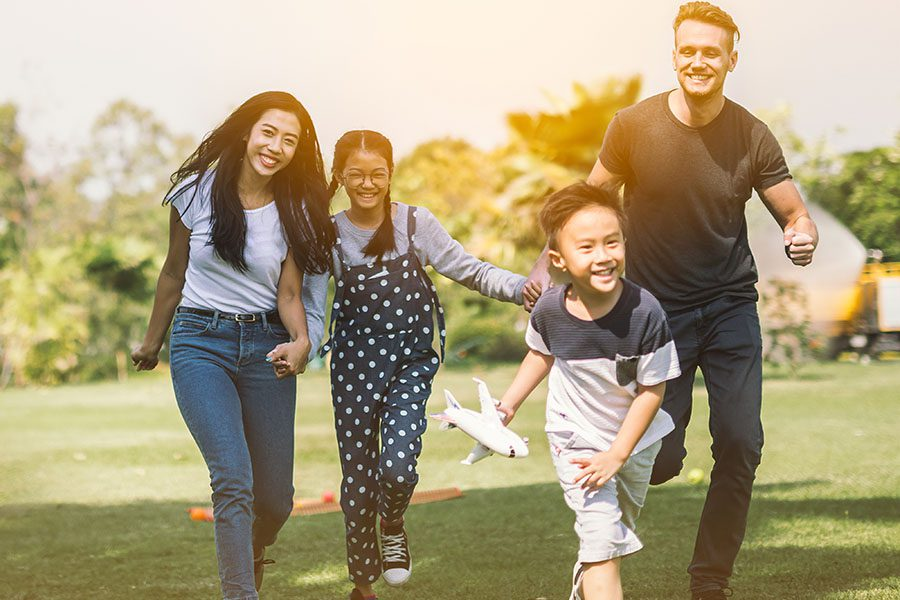 Blog - Portrait of Cheerful Family with Two Kids Running Around in the Park on a Warm Sunny Day