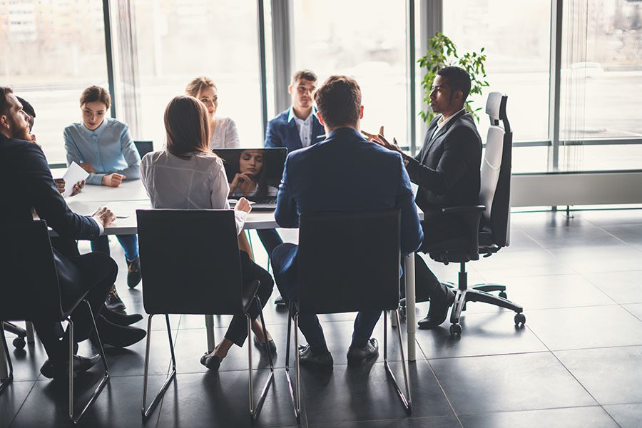 Business Insurance - Group of Employees Sitting Around a Table in a Modern Conference Room During a Corporate Business Meeting
