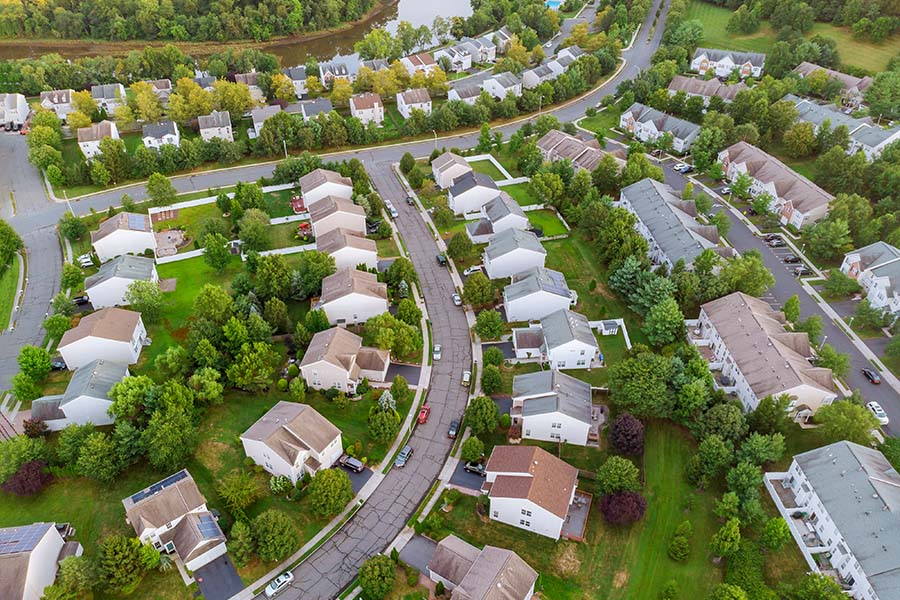 Contact - Aerial View of a Residential Neighborhood in the Suburbs Surrounded by Green Trees